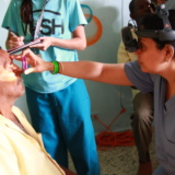 Woman giving man in the Dominican Republic an eye exam
